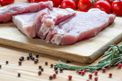 Raw pork on cutting board and vegetables Royalty Free Stock Image