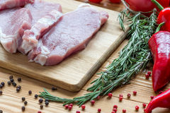 Raw pork on cutting board and vegetables Stock Image