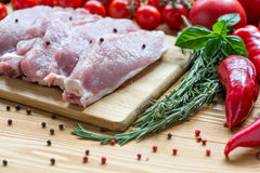 Raw pork on cutting board and vegetables Stock Photo