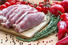 Raw pork on cutting board and vegetables. Fresh and raw meat. Pork tenderloin, loin medallions Steaks in a row ready to cook. Wooden blackboard Stock Image