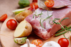 Raw pork on cutting board and vegetables. Photography of a raw pork on cutting board and vegetables Stock Photography