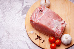 Raw pork on cutting board and vegetables. Photography of a raw pork on cutting board and vegetables Royalty Free Stock Images