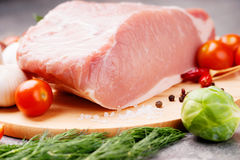 Raw pork on cutting board and vegetables. Photography of a raw pork on cutting board and vegetables Stock Photo