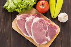 Raw pork on cutting board and vegetables on wooden background.  Royalty Free Stock Image