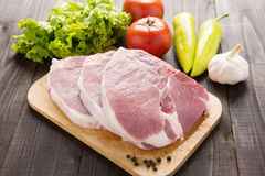 Raw pork on cutting board and vegetables on wooden background.  Royalty Free Stock Photo