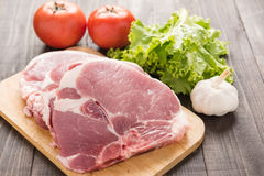 Raw pork on cutting board and vegetables on wooden background.  Stock Image