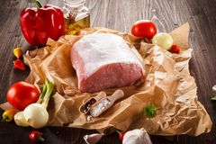 Raw pork chops on cutting board and vegetables. Raw pork on cutting board and vegetables on wooden background Royalty Free Stock Images