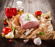 Raw pork chops on cutting board and vegetables. Raw pork on cutting board and vegetables on wooden background Stock Photography