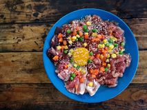 Raw pork and eggs with white sesame, corn, carrots and beans in a blue plate on an old wooden table.  stock photos