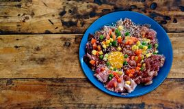 Raw pork and eggs with white sesame, corn, carrots and beans in a blue plate on an old wooden table.  stock photo
