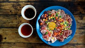 Raw pork and eggs with white sesame, corn, carrots and beans in a blue plate on an old wooden table.  stock images