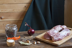 Raw pork fillet with spices and vegetables on the wood background. Selective focus Royalty Free Stock Image
