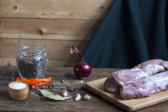 Raw pork fillet with spices and vegetables on the wood background. Selective focus Stock Photos