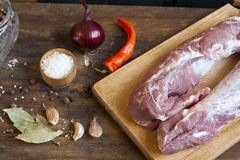Raw pork fillet with spices and vegetables on the wood background. Selective focus Stock Photography