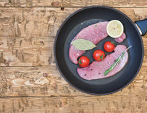 Raw pork on a frying pan on a rustic table. Ingredients for the preparation of meat dishes. Home kitchen Stock Photos