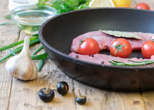 Raw pork on a frying pan on a rustic table. Ingredients for the preparation of meat dishes. Home kitchen Stock Images