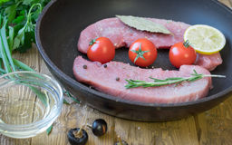 Raw pork on a frying pan on a rustic table. Ingredients for the preparation of meat dishes. Home kitchen Stock Photo