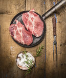 Raw pork in a frying pan with salt, fork and rosemary on rustic wooden background, top view Royalty Free Stock Images