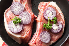 Raw pork  in a frying pan. Two pieces of raw pork chops in a frying pan Royalty Free Stock Image