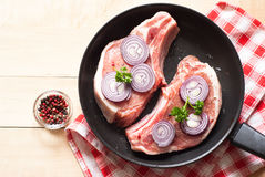 Raw pork  in a frying pan. Two pieces of raw pork chops in a frying pan. View from above with copy space Royalty Free Stock Image