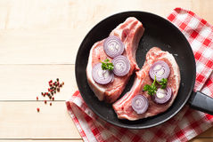 Raw pork  in a frying pan. Two pieces of raw pork chops in a frying pan. View from above with copy space Royalty Free Stock Photo
