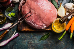 Raw pork ham meat preparation with cooking ingredients: vegetables and favoring , and meat fork on dark rustic background Royalty Free Stock Photography