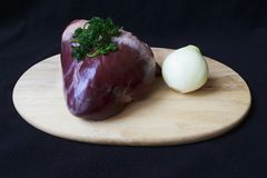 Raw pork heart on board. Picture taken 10 November 2015 in Jablonec nad Nisou, Czech Republic, heart parsley raw pork with onions on a cutting board dark Royalty Free Stock Photography