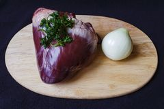 Raw pork heart on board view. Picture taken 10 November 2015 in Jablonec nad Nisou, Czech Republic, heart parsley raw pork with onions on a cutting board dark Stock Images