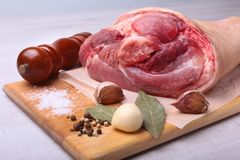 Raw pork knuckle, Aromatic dried bay leaves, garlic, sea salt, pepper grinder and spices on a cutting board. Selective. Focus. Ready for cooking Royalty Free Stock Image