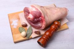 Raw pork knuckle, Aromatic dried bay leaves, garlic, sea salt, pepper grinder and spices on a cutting board. Selective. Focus. Ready for cooking Royalty Free Stock Photo