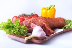 Raw pork knuckle and vegetables, garlic, tomatoes, bell pepper. spices and lettuce leaves on a cutting board. Selective