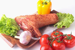 Raw pork knuckle and vegetables, garlic, tomatoes, bell pepper. spices and lettuce leaves on a cutting board. Selective. Focus. Ready for cooking Royalty Free Stock Photography