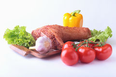 Raw pork knuckle and vegetables, garlic, tomatoes, bell pepper. spices and lettuce leaves on a cutting board. Selective. Focus. Ready for cooking Stock Photo
