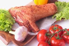 Raw pork knuckle and vegetables, garlic, tomatoes, bell pepper. spices and lettuce leaves on a cutting board. Selective. Focus. Ready for cooking Royalty Free Stock Image