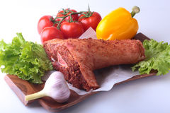 Raw pork knuckle and vegetables, garlic, tomatoes, bell pepper. spices and lettuce leaves on a cutting board. Selective Royalty Free Stock Photos