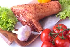Raw pork knuckle and vegetables, garlic, tomatoes, bell pepper. spices and lettuce leaves on a cutting board. Selective. Focus. Ready for cooking Royalty Free Stock Images