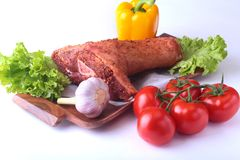 Raw pork knuckle and vegetables, garlic, tomatoes, bell pepper. spices and lettuce leaves on a cutting board. Selective. Focus. Ready for cooking Stock Photos