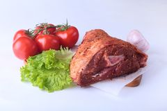 Raw pork knuckle and vegetables, garlic, tomatoes spices and lettuce leaves on a cutting board. Selective focus. Ready. For cooking Royalty Free Stock Images
