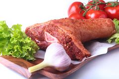 Raw pork knuckle and vegetables, garlic, tomatoes spices and lettuce leaves on a cutting board. Selective focus. Ready