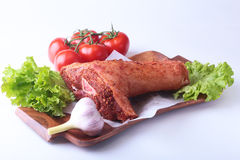 Raw pork knuckle and vegetables, garlic, tomatoes spices and lettuce leaves on a cutting board. Selective focus. Ready. For cooking Stock Images