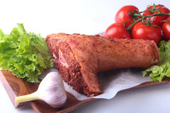 Raw pork knuckle and vegetables, garlic, tomatoes spices and lettuce leaves on a cutting board. Selective focus. Ready. For cooking Stock Photo