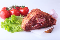 Raw pork knuckle and vegetables, garlic, tomatoes spices and lettuce leaves on a cutting board. Selective focus. Ready. For cooking Stock Photos