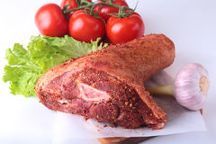 Raw pork knuckle and vegetables, garlic, tomatoes spices and lettuce leaves on a cutting board. Selective focus. Ready. For cooking Royalty Free Stock Photo
