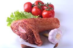 Raw pork knuckle and vegetables, garlic, tomatoes spices and lettuce leaves on a cutting board. Selective focus. Ready. For cooking Stock Image