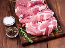 Raw Pork Loin chops on a cutting board with herbs rosemary on dark wooden background, side view. Raw Pork Loin chops on a cutting board with herbs rosemary on a Royalty Free Stock Image