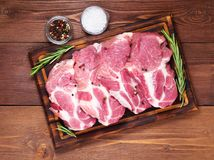 Raw Pork Loin chops on a cutting board with herbs rosemary on dark wooden background, top view. Raw Pork Loin chops on a cutting board with herbs rosemary on a Royalty Free Stock Photography