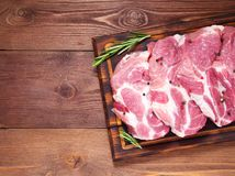 Raw Pork Loin chops on a cutting board with herbs rosemary on dark wooden background, top view, copy space. Raw Pork Loin chops on a cutting board with herbs Stock Photos