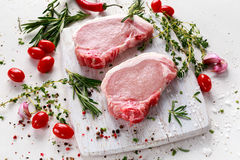 Raw Pork Loin chops on a cutting board with herbs, rosemary, thyme, chilli, salt, pepper on white cutting board. Royalty Free Stock Image