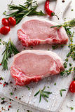 Raw Pork Loin chops on a cutting board with herbs, rosemary, thyme, chilli, salt, pepper on white cutting board. Royalty Free Stock Photo