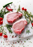 Raw Pork Loin chops on a cutting board with herbs, rosemary, thyme, chilli, salt, pepper on white cutting board. Royalty Free Stock Images
